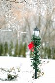 stock photo of winter scene  - A winter scene with street post wrapped in greenery and Christmas bow - JPG
