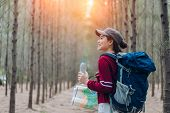 Asia Woman Travel With Backpack,map At Forest Holding Water Go To Destinations, Girl Traveler Doing  poster