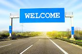 Blue Freeway Sign Over The Road On Sunny Day With Word Welcome On It poster