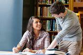 Jóvenes estudiantes ayudando uno al otro haciendo un ensayo