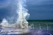 Huge breaking stormy wave. Big wave. The big wave is breaking about the shore. Rainbow poster
