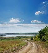 rural road near river under cloudy sky