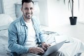 Professional Freelancer. Delighted Cheerful Smart Man Sitting On The Bed And Using His Laptop While  poster