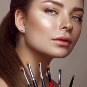 Beautiful Young Girl With Natural Nude Make-up With Cosmetic Tools In Hands. Beauty Face. Photo Take poster