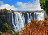 Постер, плакат: Victoria Falls mosi o tunya Taken From The Zimbabwe Side Overlooking Zambia With A Blue Cloudy S