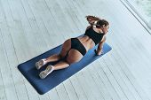 Relaxing Exercise. Top View Of Young Woman In Sport Clothing Standing On The Exercise Mat While Spen poster