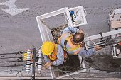 Two Electricians Worker Working In The Cradle Of The Manipulator Safety Belt Forklift Man-lift Safet poster
