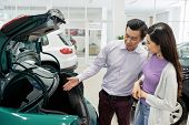 Asian Couple Discussing Small Trunk Of Car Automobile In Car Dealership poster