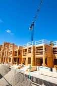 New Residential Building Under Construction With The Crane Above. Low Rise Wooden Framework Of The B poster