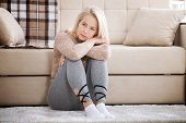 Depression. Middle Aged Barefoot Woman Sitting At The Floor Embracing Her Knees, Near Sofa At Home,  poster