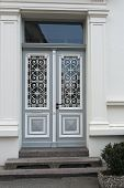 pic of woodcarving  - Grey double door with woodcarvings and decoration on windows - JPG