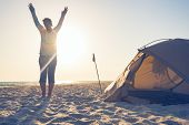 Joyful Woman Traveler, With Open Arms, Standing Next To Tent On The Seaside And Admiring Setting Sun poster