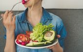 Young Woman Eating Fresh Vegetables At Home. Vegan Eating Avocado, Salad, Radish And Tomatos poster