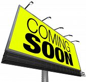 The words Coming Soon on a large outdoor billboard on a yellow background advertises a new store, gr
