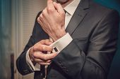 Man Is Putting On Cuff-links As He Gets Dressed In Formal Wear Close Up poster