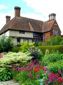 image of english cottage garden  - English country house with summer flower border in front and blue sky and white clouds behind - JPG