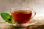 Cup Of Hot Mint Tea With Fresh Green Juicy Mint Leaves. Aromatic Tea In A Glass Cup On Vintage Woode poster