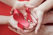 Hands Holding Red Ribbon On Red Background, Hiv Awareness Concept, World Aids Day, World Hypertensio poster