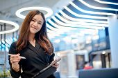 Working Woman Concept. Attractive Young Asian Businesswoman Using Digital Tablet Smiling In Modern O poster