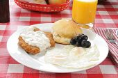 stock photo of biscuits gravy  - A chicken fried steak smothered in country gravy wiht fried eggs - JPG