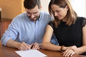 Pleasant Young Woman Watching Smiling Husband Signing Contract. poster
