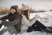 Happy Winter Couple Smiling Having Fun Like Children In Winter Park Near A Snowy River. Young Beauti poster