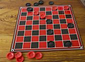 picture of boardgame  - a game of checkers in progress with a checker board on a wooden table - JPG