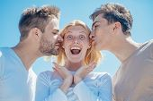 Blonde Happy Girl Getting Kisses From Two Handsome Boys. Charming Woman Standing Between Two Friends poster