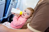 Father Holding Baby Daughter During Flight On Airplane Going On Vacations. Baby Girl Drinking Formul poster