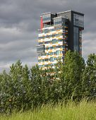 stock photo of urbanisation  - Modern skyscraper appearing behind meadows and trees - JPG