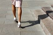 Slim Female Legs On High Heels, Woman In Pink Skirt Walking On A Street, Shadow On Steps. Concept Of poster