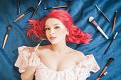 Pretty Woman With Red Hair Lying With Make Up Brushes And Dreaming, Top View Girl Make Up Master On  poster