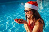 New Year And Christmas Holiday. Woman In Santas Hat And Bikini Eating Strawberries In Swimming Pool. poster