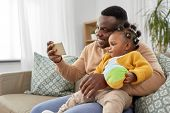 family, fatherhood and people concept - happy african american father with little baby daughter taki poster