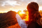 Carefree hipster girl enjoying sunset on top of mountain. Image of freedom concept. Model meditates  poster