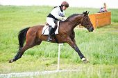 Woman eventer on horse is overcomes the open ditch