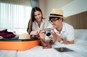 Happy Asian Couple Unpacking Suitcase On Bed In Bedroom When They Arrive In Hotel Room And Lying And poster