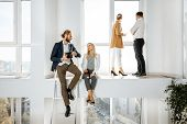 Group Of A Young Creative Office Employees Having Some Informal Discussion, While Standing In The Tw poster