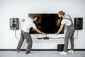 Two Professional Workmen In Workwear Installing A Large Tv Monitor And Audio System In The White Liv poster