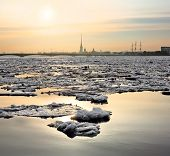 Spring Ice Floes On The River Neva In Saint Petersburg. View Of The Peter And Paul Fortress In Sunse