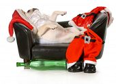 drunk santa - french bulldog santa laying on couch with wine bottle at feet isolated on white background