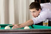 Young male playing billiards. Spending free time on gambling