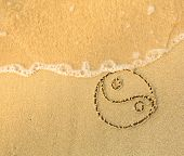 Yin yang symbol - written in sand on beach texture - soft wave of the sea