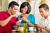 Asian people having fun together with mobile phone and drinking coffee or cocktail