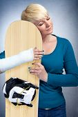 Woman with broken arm hugging her snowboard, I love snowboarding