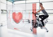 picture of electrocardiogram  - Young girl doing exercise bike with futuristic interface showing electrocardiogram - JPG