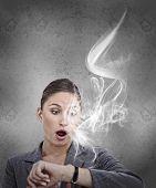 Businesswoman realising she is late bu looking at smoking wrist watch