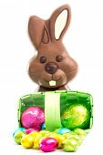 Easter eggs spilling from a green wicker basket with chocolate bunny