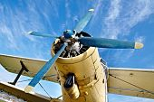 stock photo of propeller plane  - Engine of an old airplane from low angle - JPG