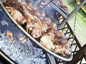pic of brazier  - roasted pork knuckle on large brazier in country fair - JPG